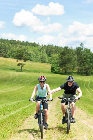 Sport mountain biking - man pushing young girl uphill sunny countryside photo