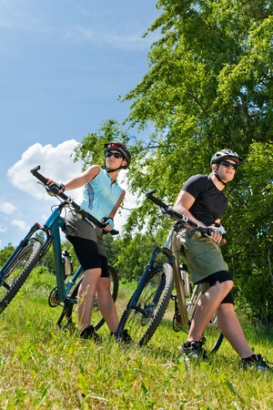 Sport mountain biking happy couple relax in meadows sunny countryside photo