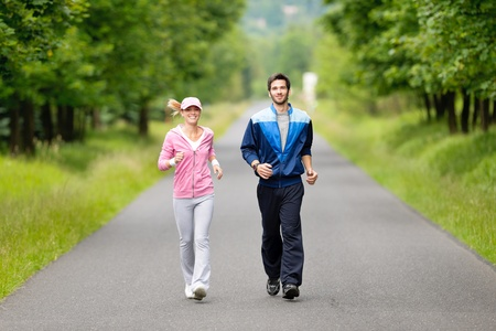 tracksuit: Jogging young fit couple running park road in sportswear tracksuit
