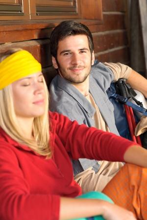 tramping: Excursionismo de mochila de la joven pareja relajarse sentado por caba?a de madera
