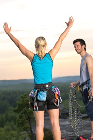 Rock climbing cheerful active young mountaineers reach top at sunset photo