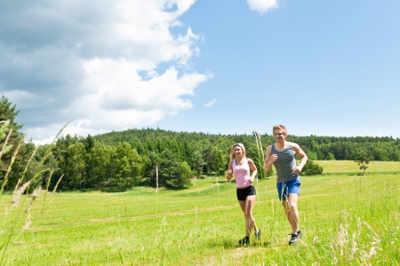 jogging in park: Young fit couple jogging on summer day in meadows countryside
