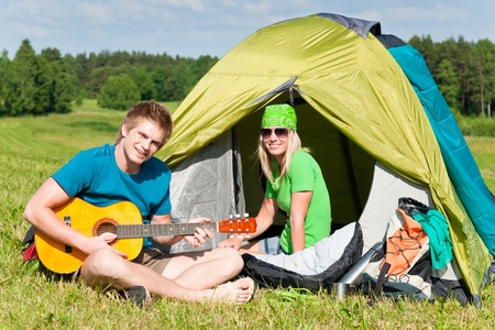 Happy camping couple sitting by tent play guitar sunny countryside photo