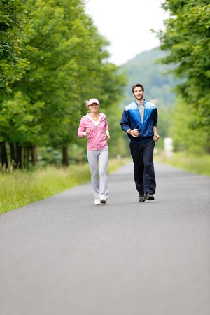 Jogging young fit couple running park road in sportswear tracksuit photo