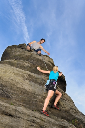 rock climb: Rock climbing active young woman  man holding rope on top Stock Photo