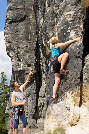 to climb: Rock climbing male instructor hold rope blond woman sunny day