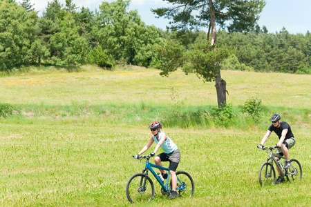 Sport happy couple riding bicycles in coutryside meadows photo