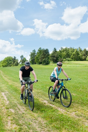 coutryside: Sport couple riding mountain bicycles in coutryside meadows