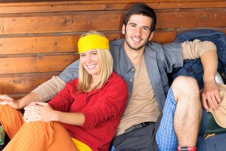 tramping: Excursionismo de mochila de la joven pareja relajarse sentado por la caba�a de madera