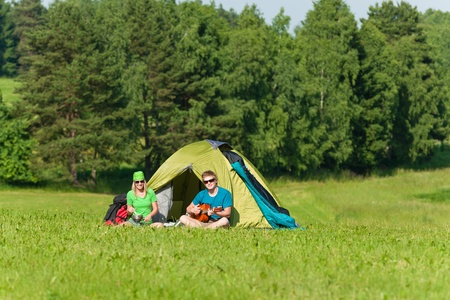 Young camping couple cooking meal play guitar in sunny countryside photo