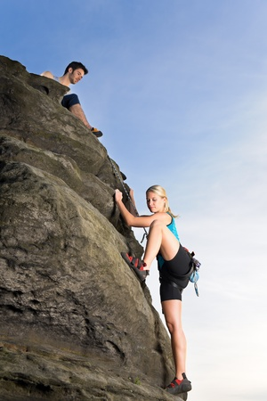 Rock climbing active young woman  man holding rope on top photo
