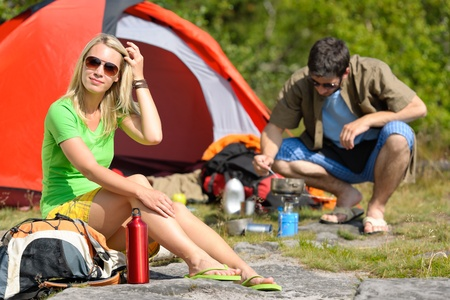 Happy camping couple with tent backpack cooking in sunny countryside photo