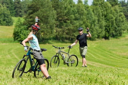 Sport mountain biking happy couple greeting in meadows sunny countryside photo
