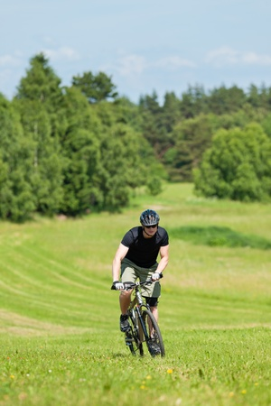 coutryside: Fit young man cycling uphill mountain bike in summer coutryside Stock Photo