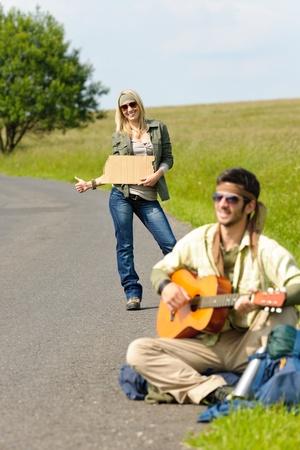 tramping: Autostop mochila joven pareja caminando sobre tocar la guitarra carretera de asfalto
