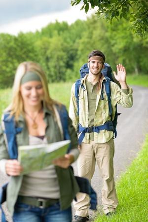 tramping: Paseos mochila joven pareja caminando sobre la carretera de asfalto rural Foto de archivo