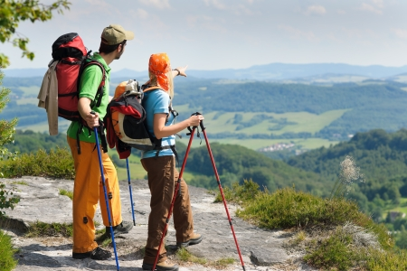 backpackers: Young backpack couple with hiking poles beautiful panoramic view countryside