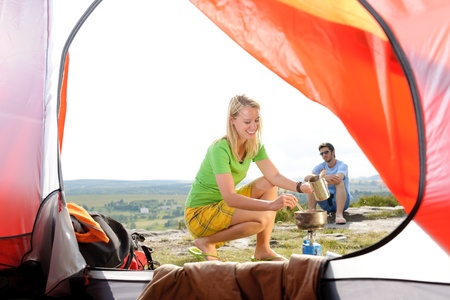 Camping young couple outside tent cook meal countryside view photo