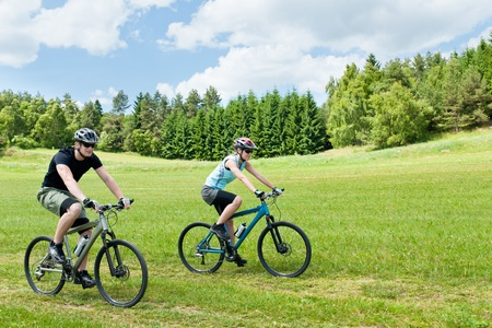 cycling   helmet: Sport happy couple riding bicycles in countryside meadows