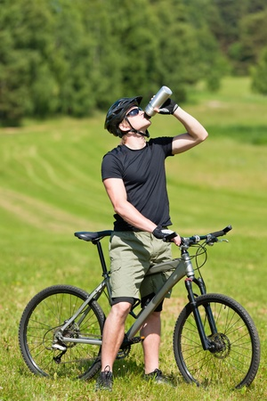 Fit young cycling man relax drink water in summer countryside