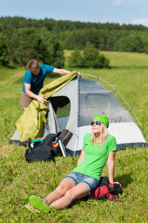 Young camping couple build-up tent in summer meadows countryside photo