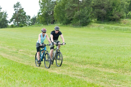 coutryside: Sport happy couple riding bicycles in coutryside meadows