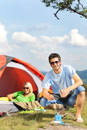 holiday cooking: Happy camping couple with tent backpack cooking in sunny countryside
