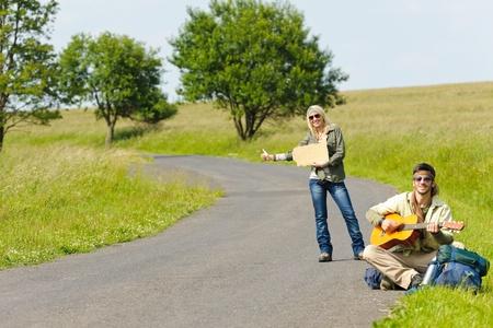 tramping: Enganche-alza de excursionismo de mochila de joven pareja en la guitarra de obra carretera de asfalto Foto de archivo