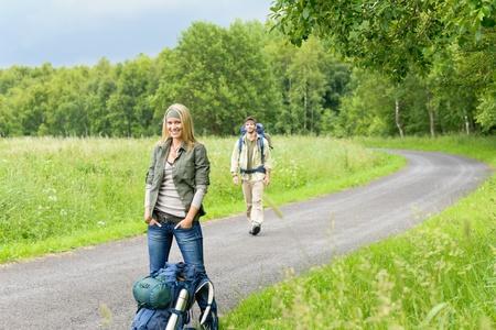 tramping: Pareja joven de senderismo mochila senderismo en el campo de la carretera de asfalto