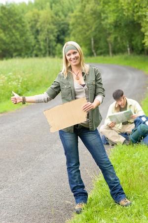 tramping: Hitch-caminata de excursionismo de mochila de pareja en la guitarra de juego de carretera de asfalto