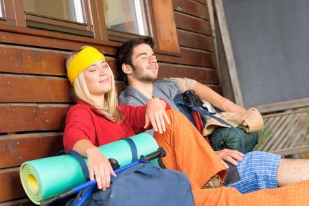 tramping: Tramping joven pareja mochila dormir sentado por caba�a de madera