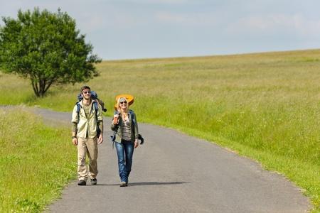 tramping: Mochila de joven pareja senderismo excursionismo en campo soleado de la carretera de asfalto