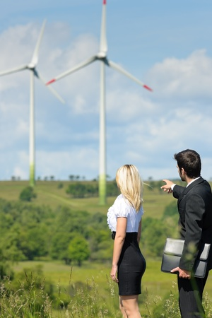 Green energy businesspeople - Young businesswoman pointing at windmill in field photo