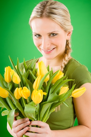 Young blond woman hold yellow tulips flower on green photo