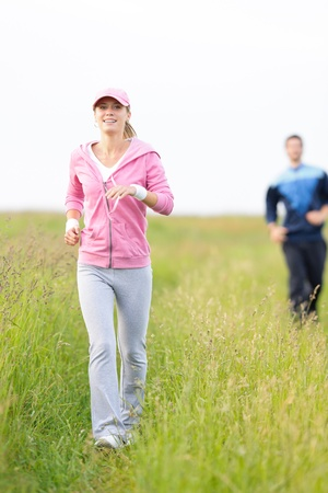 tracksuit: Jogging young fit couple running field meadow in sportswear tracksuit