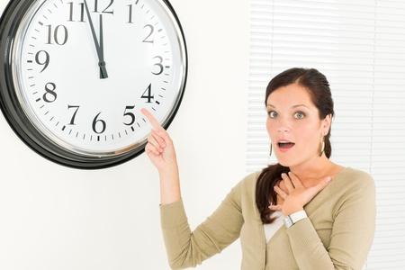stipt: Stipte zakenvrouw jonge aantrekkelijke wijzend op klok portret