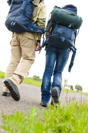 rucksacks: Close-up of hiking couple legs backpack on asphalt road Stock Photo