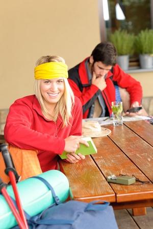 tramping: Excursionismo de mochila de la joven pareja relajarse sentado por caba�a mesa de madera Foto de archivo