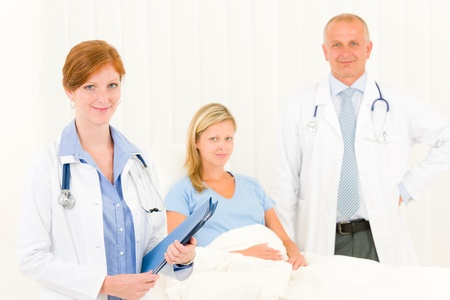 Two medical doctors professional with hospital patient lying in bed Stock Photo - 10082506