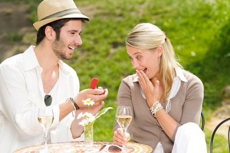 Young man proposing to girlfriend offering engagement ring sunny terrace photo