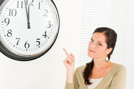punctual: Joven empresaria puntual atractivo apuntando al retrato de reloj