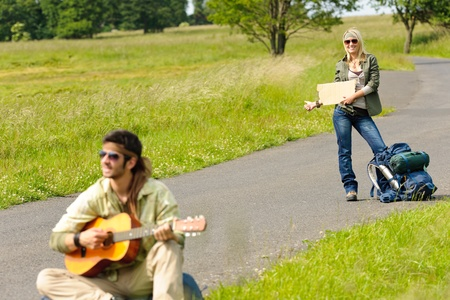 Hitch-hike young couple backpack tramping on asphalt road play guitar photo
