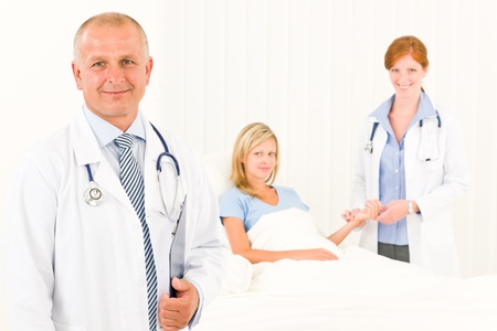 Two medical doctors with patient lying in bed examine pulse Stock Photo - 10082522