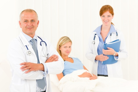 Two medical doctors professional with hospital patient lying in bed Stock Photo - 10082521