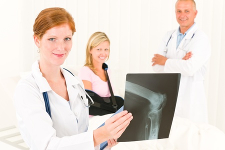 Medical doctors show x-ray hospital patient in bed broken arm Stock Photo - 10082524