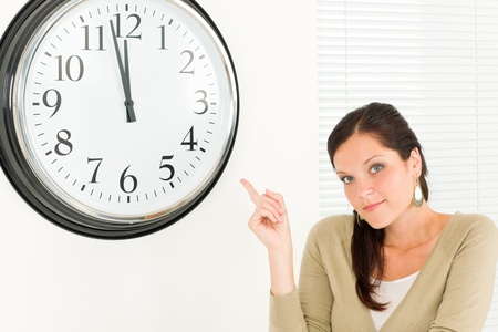 punctual: Punctual businesswoman young attractive pointing at clock portrait Stock Photo