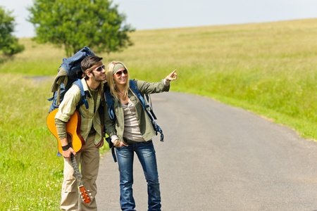tramping: Hiking young couple backpack tramping on asphalt road sunny countryside Stock Photo