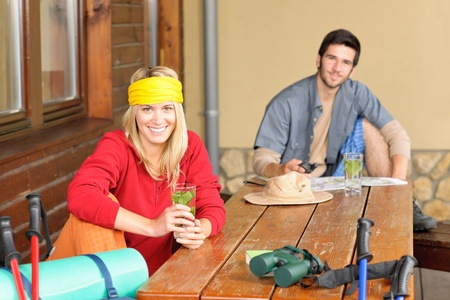 tramping: Tramping young couple backpack relax by wooden table drink water