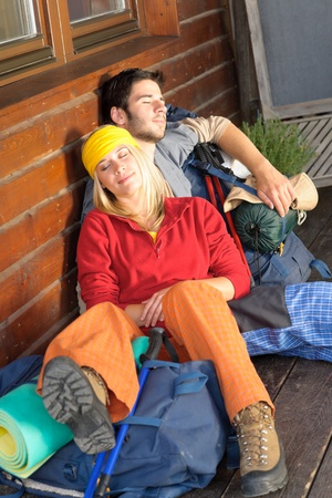 tramping: Tramping young couple backpack sleep sitting by wooden cottage