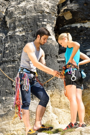 woman rope: Rock climbing active young man showing mountaineer woman rope knot